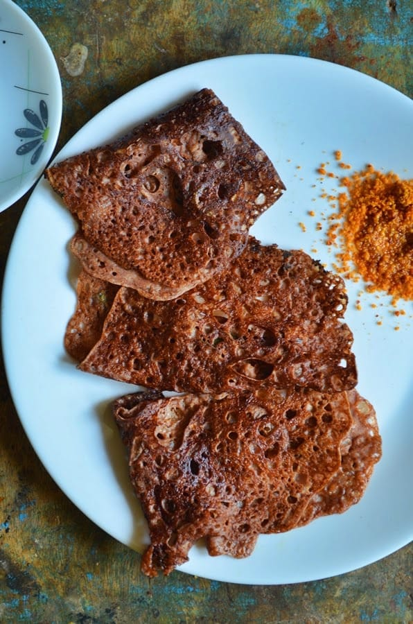 Ragi dosa- crispy and tasty instantly made sprouted finger millet dosa served on a white plate with dry chutney powder.