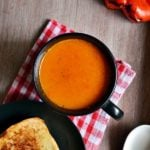 A black mug containing roasted red bell pepper soup served with toasted bread for dinner.