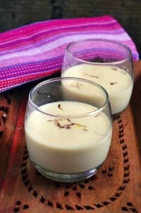 homemade thandai served in short glasses on a wooden tray