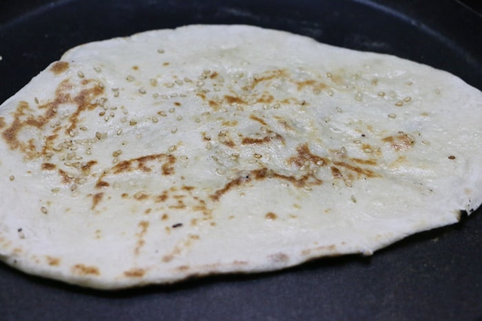 butter naan sprinkled with sesame seeds and slathered with butter,