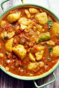closeup short of Indian vegan potato curry in a green enamel pan.