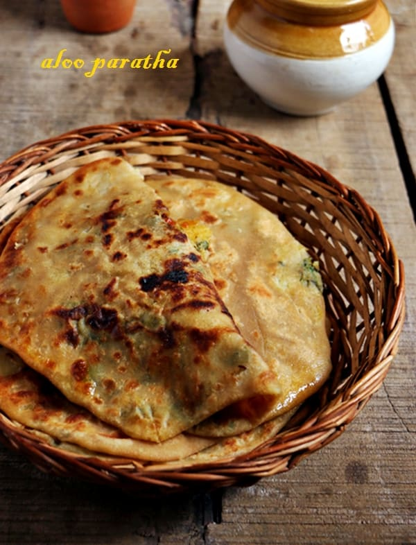 Punjabi aloo paratha served with curd and mango pickle for breakfast
