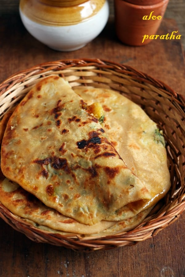 dhaba style aloo paratha served in a bamboo tray with pickle and tea