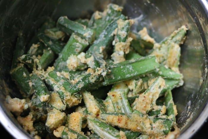 Making Kurkuri Bhindi Recipe- mixing okra with flours