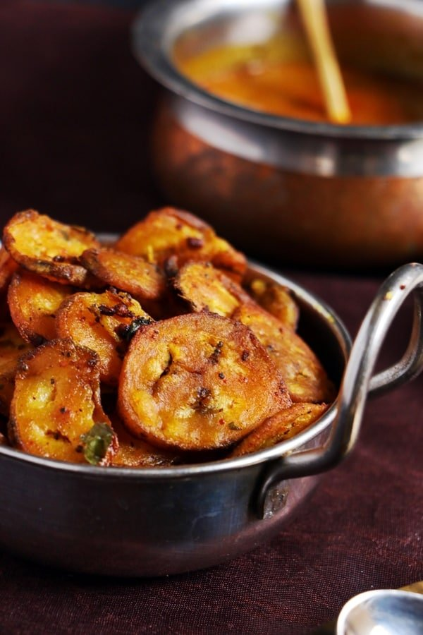 Crispy raw banana fry served in silver pan with sambar for lunch