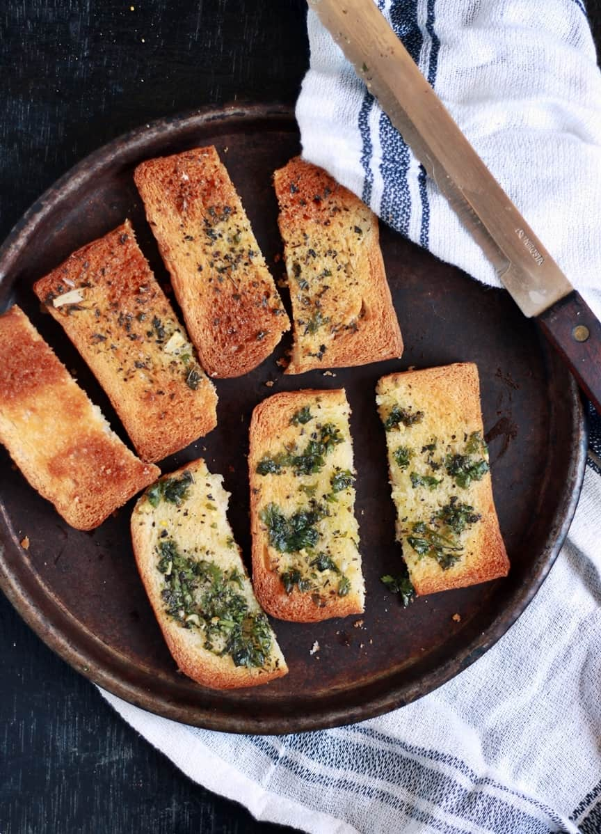 Crisp garlic toast served in a metal plate for snack
