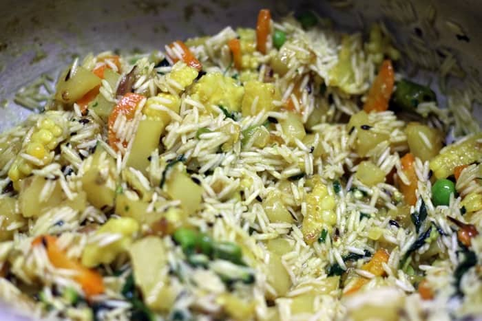 Adding basmati rice to sauteed veggies.