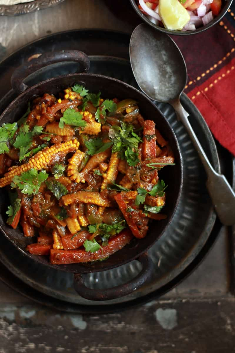 Closeup shot of vegetable jalfrezi curry served in a cast iron pan with roti for dinner