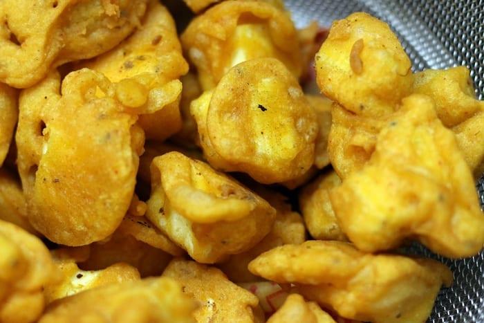 fried paneer pakora in a strainer