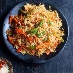 homemade schezwan fried rice in a black ceramic plate