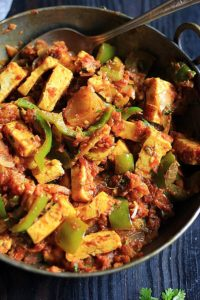 restaurant style kadai paneer served in a copper pan with a spoon.