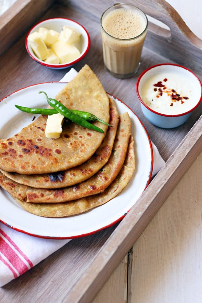 Fresh homemade aloo paratha stcaked with some butter and served with chai, dahi and more butter on a wooden tray