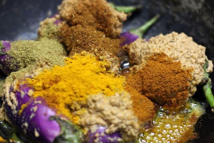 Adding spice powders to eggplants for making bharli vangi recipe