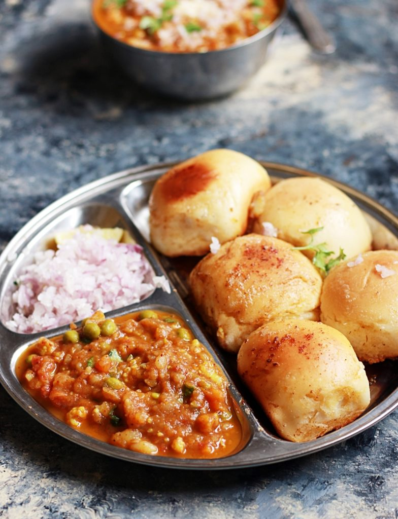 pav bhaji served in a steel sectioned plate with raw onions