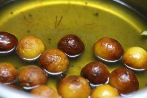 soaking gulab jamun made with milk powder in sugar syrup