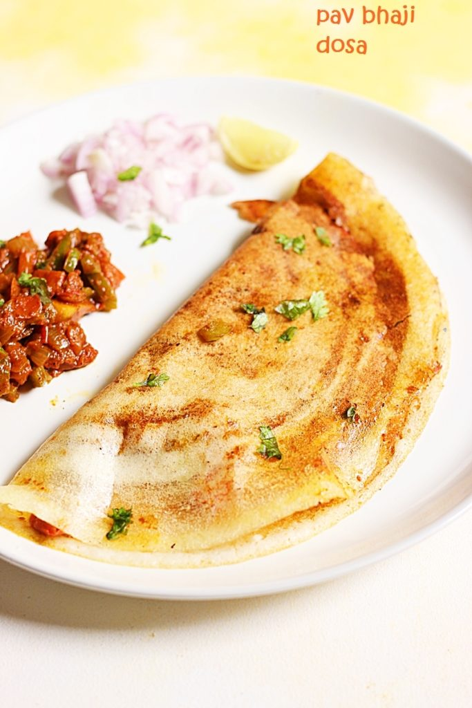 crispy pav bhaji dosa served with a side of onions and spicy bhaji