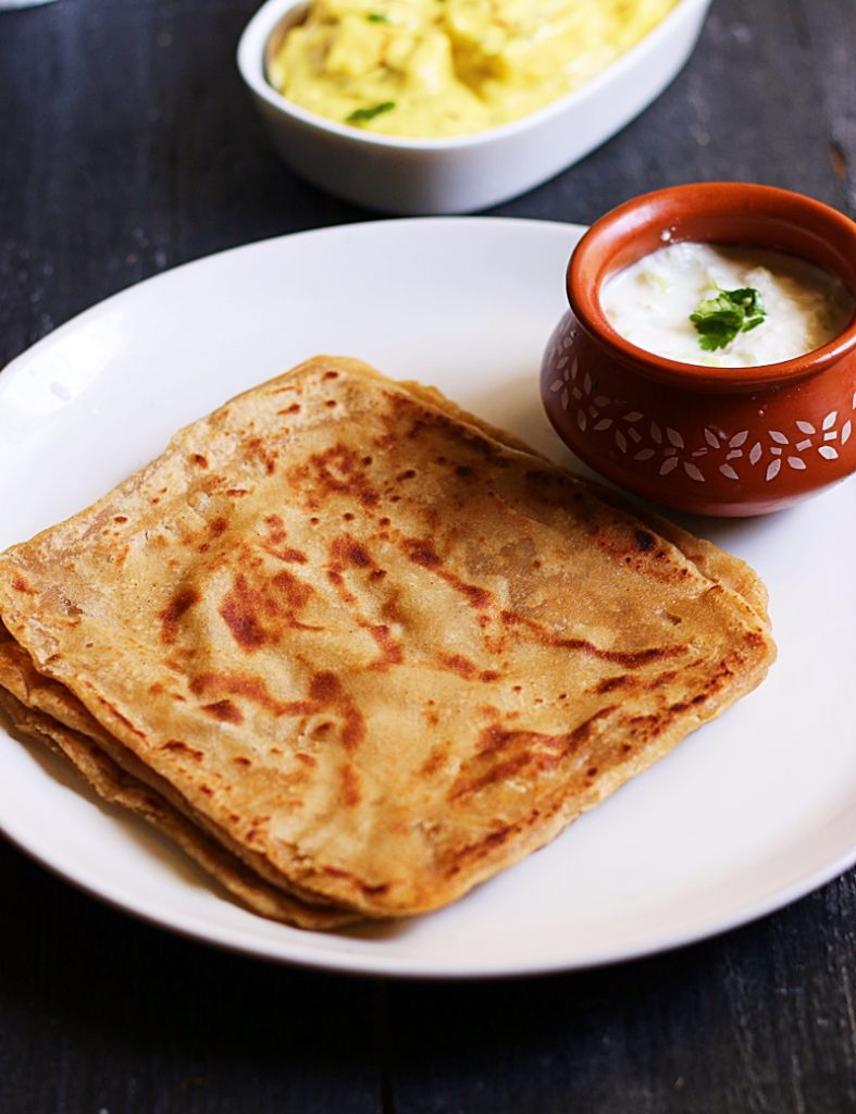 soft flaky parathas stacked in a white plate and served with yogurt and shahi paneer
