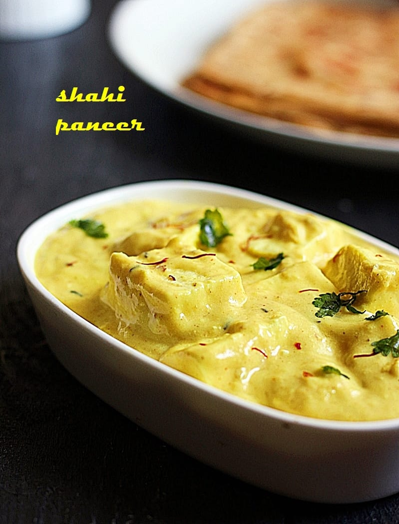 creamy shahi paneer topped with saffron strands served in a ceramic dish.