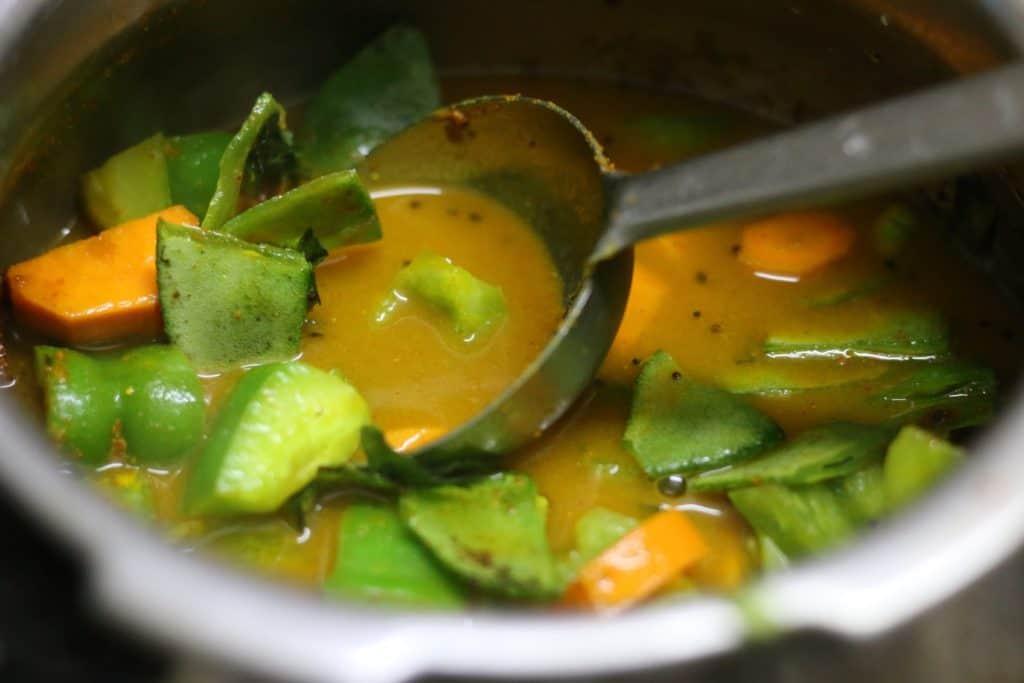 adding veggies for making poricha kuzhambu recipe