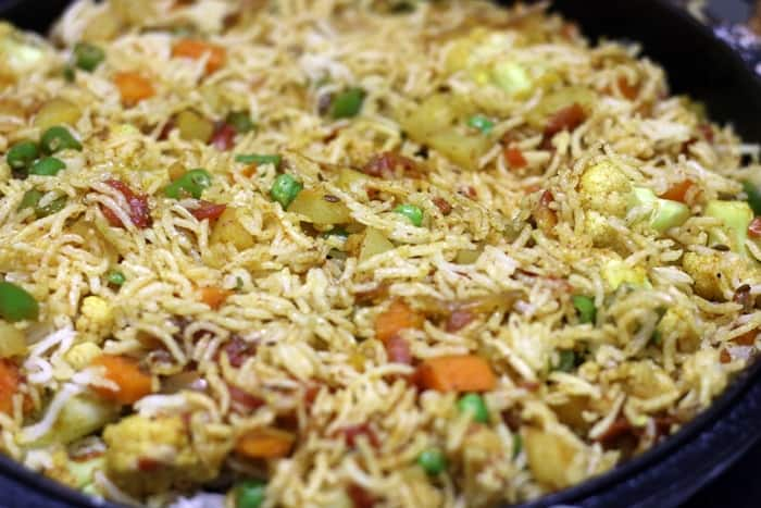 tossing rice with veggies- making tawa pulao