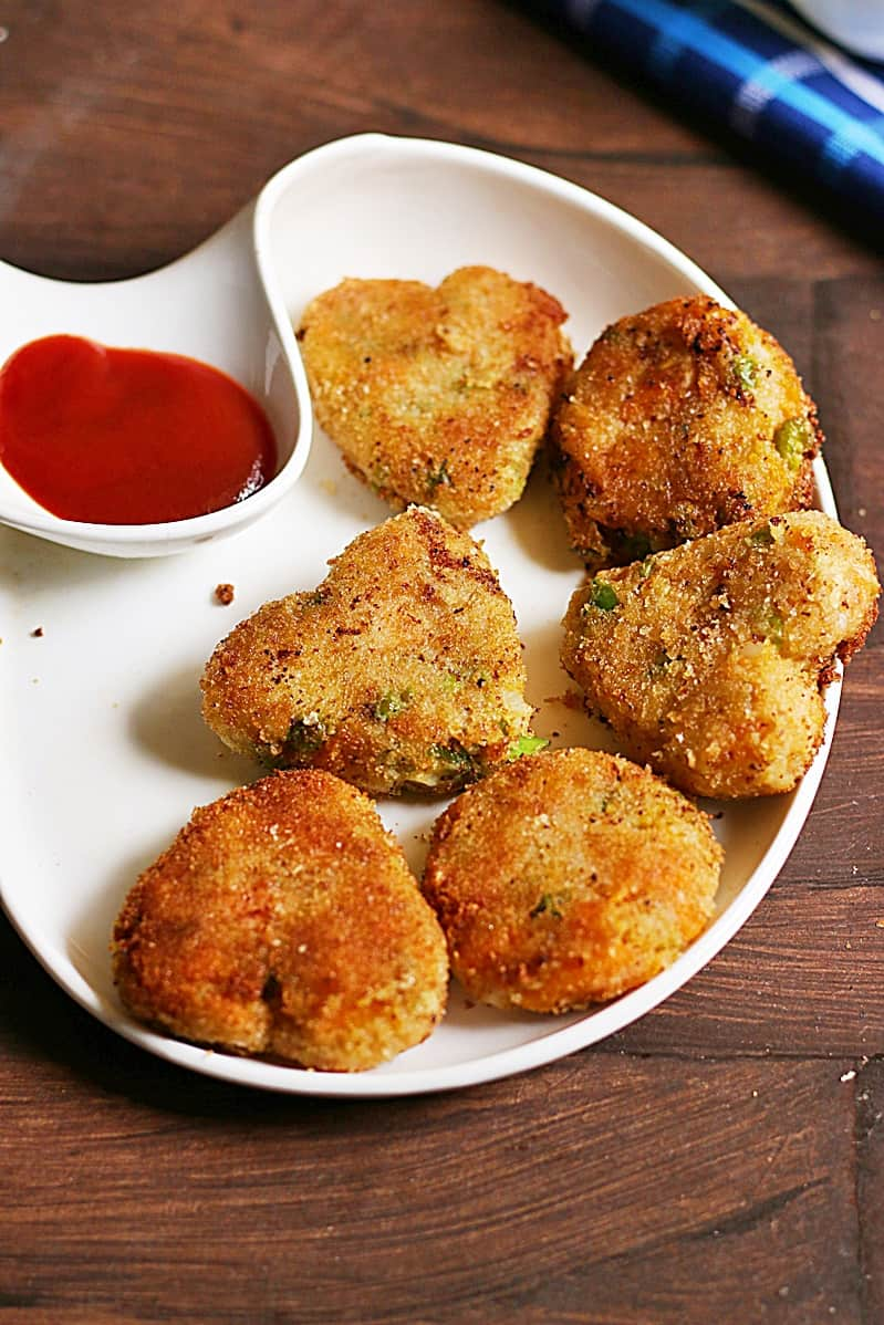 Fresh vegetable cutlets served in a chip n dip plate with ketchup