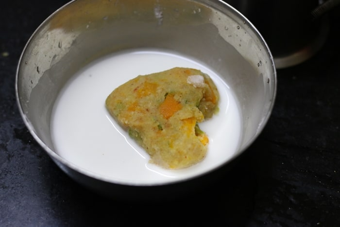 Dipping the shaped veg patty in corn flour slurry for making vegetable cutlet recipe.