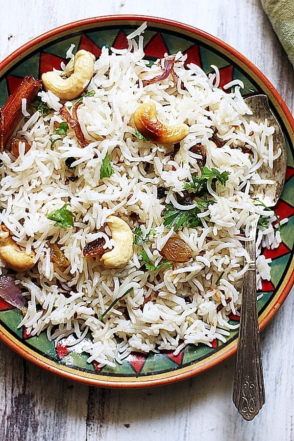 overhead shot of ghee rice garnished with fried cashews and raisins