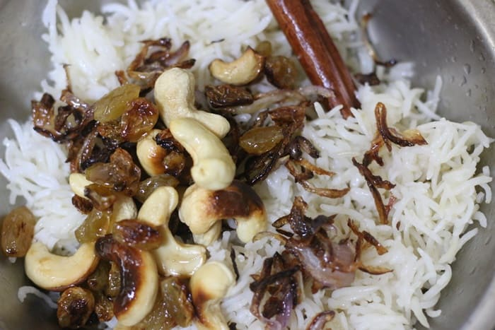 adding fried cashews and raisins to cooked ghee rice