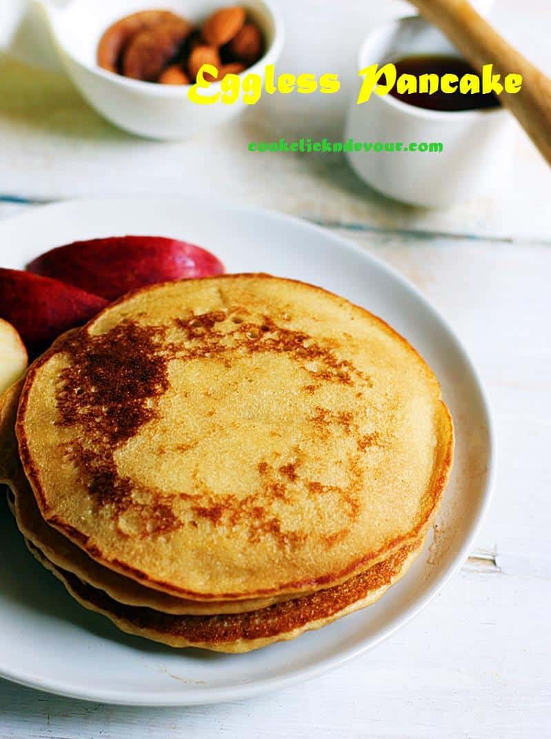 Fluffy, soft and tasty eggless pancakes served on a white plate for breakfast along with honey and fruits.
