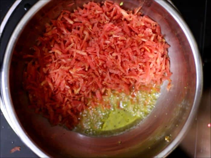 sauteing grated carrots in ghee for carrot halwa recipe