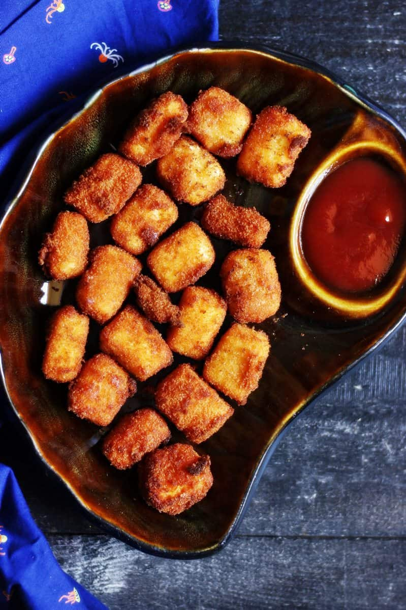 Paneer popcorn recipe- A brown plate with crispy and tasty paneer pops served with sauce.