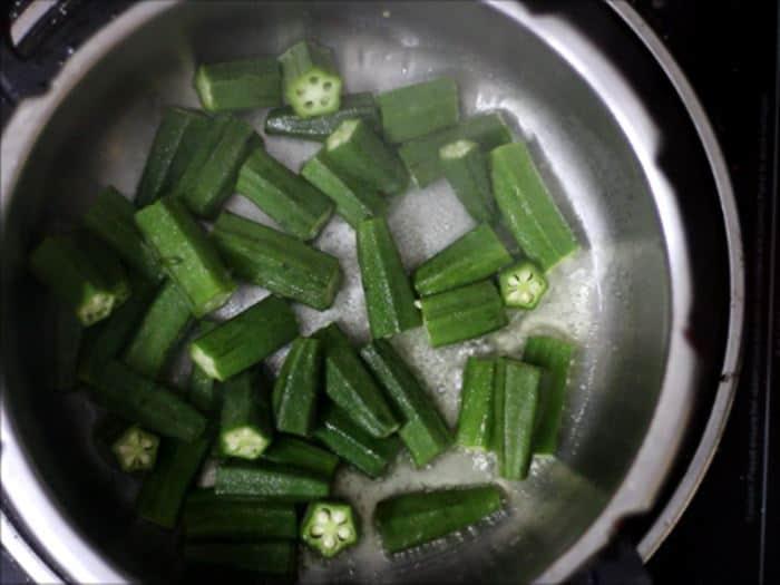 sauteing okra for dahi bhindi recipe, dahi wali bhindi recipe