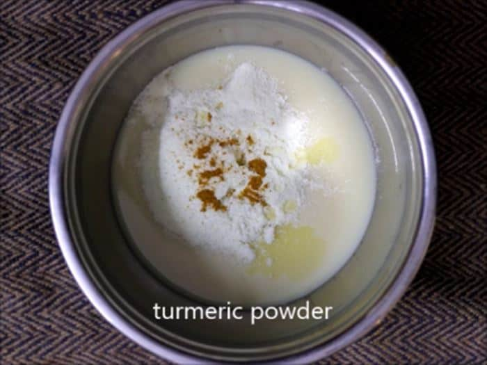 Condensed milk, turmeric milk and milk powder combined in a mixing bowl.