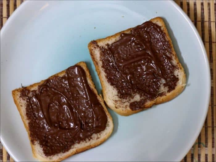 Spreading nutella on bread slices for chocolate sandwich