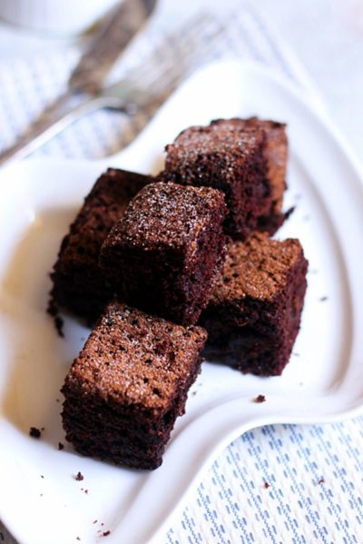 small squares of eggless chocolate cake dusted with sugar served on a white snack plate.