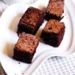 eggless chocolate cake recipe- wacky cake squares served on a white snack plate.