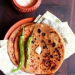 tasty paneer paratha served on bron plate with fried chilies, butter and thick curd for breakfast!