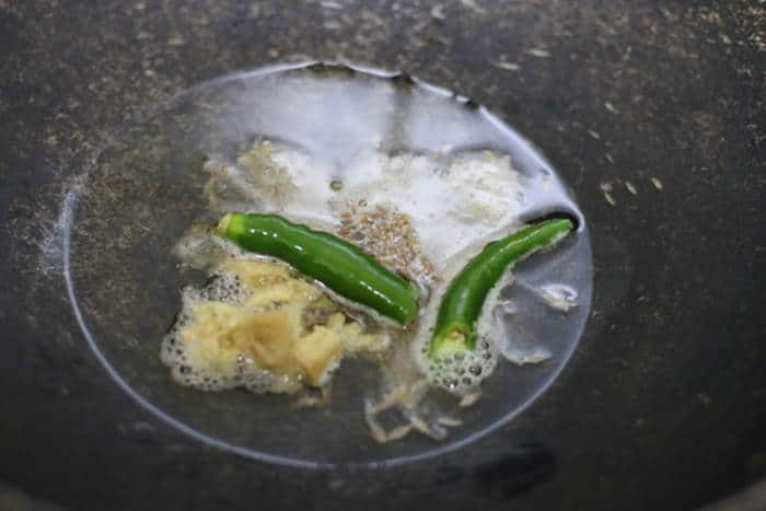 sauteing ginger garlic and green chili in oil