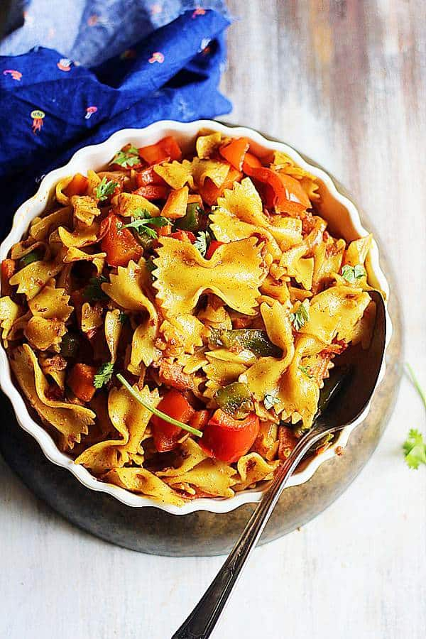 Indian style masala pasta served in a shallow white dish with a metal spoon