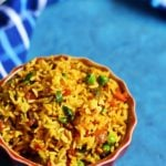 quick and easy masala rice recipe served in a red rice bowl for lunch with a spoon