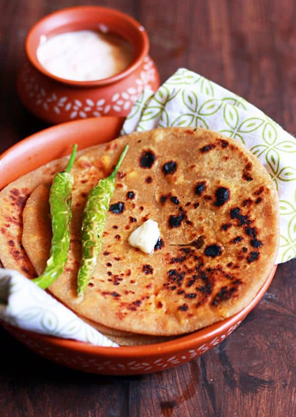 wholesome and delicious Punjabi Paneer Paratha served on brown plate with fried chilies and a dab of butter. Some thick yogurt in a small bowl is served as side dish.