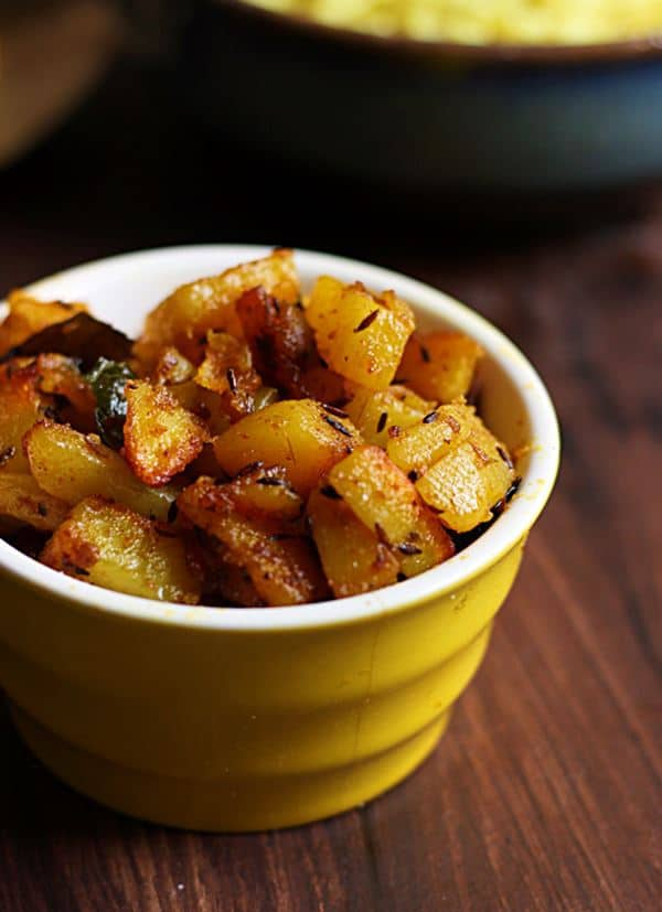 easy to make jeera aloo served in a small ceramic bowl with rice