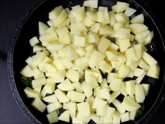 adding cubed potatoes for jeera aloo recipe