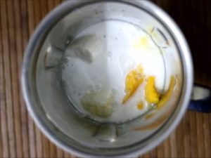 Coconut milk added to sliced bananas and mangoes