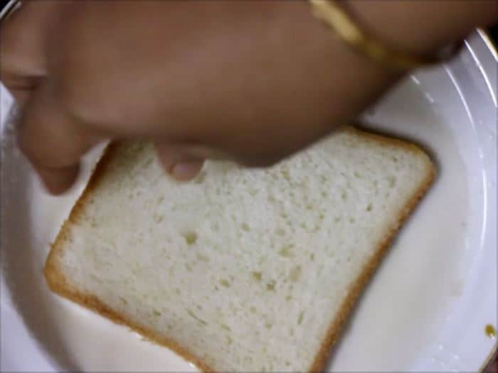 dipping bread slice in sweet milk to make milk toast