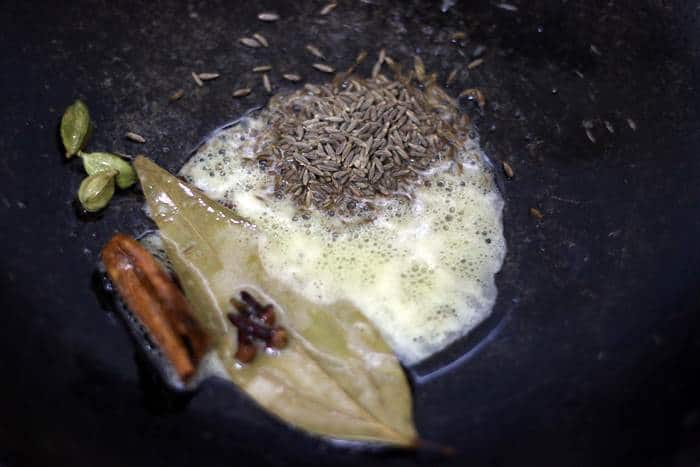 sauteing cumin seeds in ghee for making zeera rice