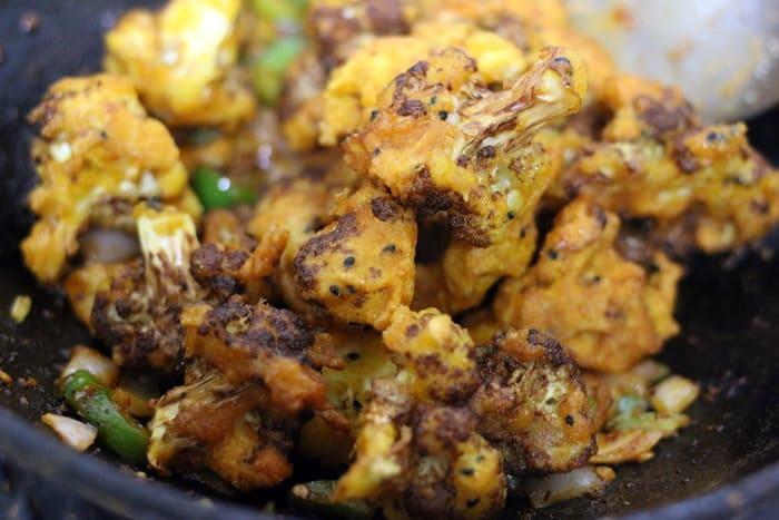 tossing fried gobi in sauce to finish making gobi manchurian