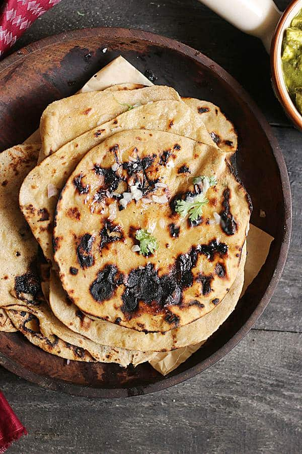 Homemade soft tandoori roti stacked in a wooden plate.