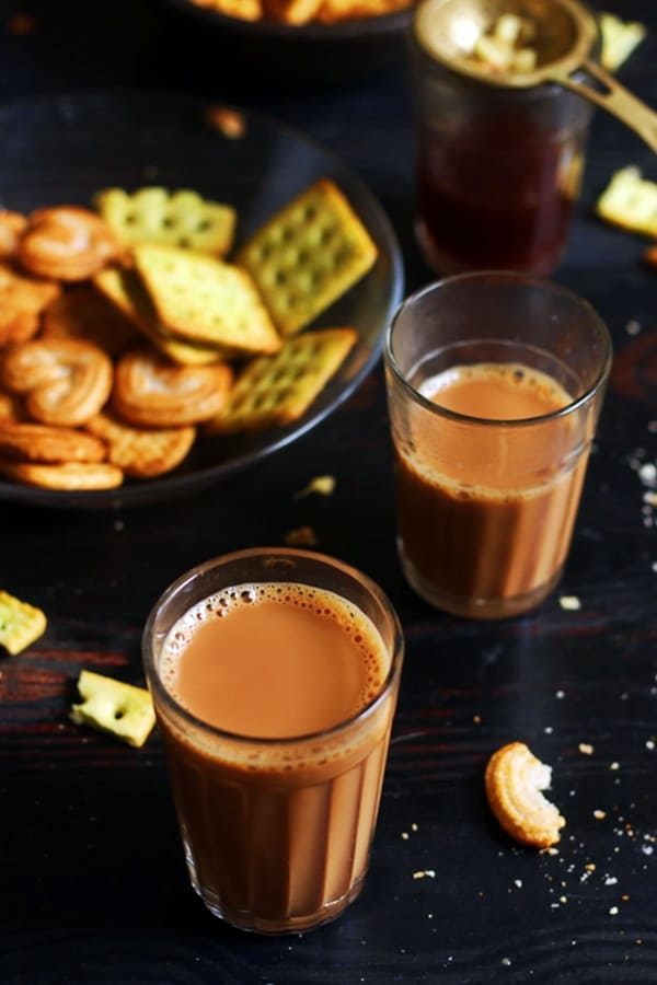 Indian adrak chai served in glass tumblers with snacks and biscuits