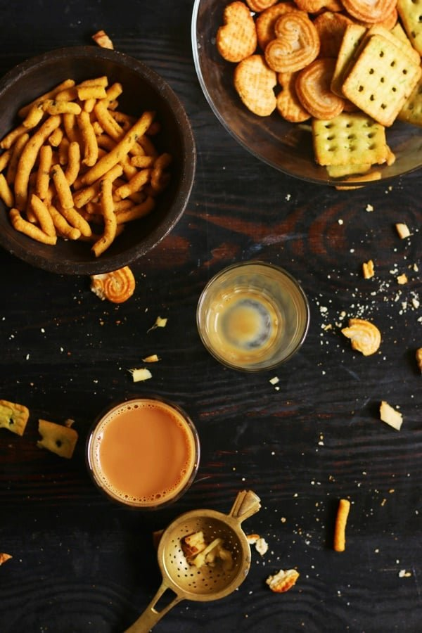 Overhead shot of indian ginger tea or adrak chai served with snacks and biscuits